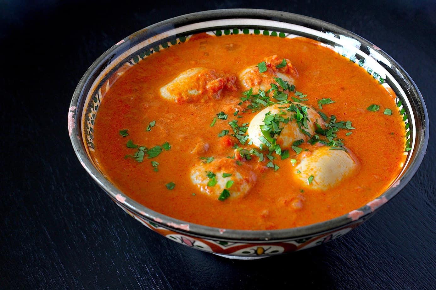 Sambal goreng telor (pittige eieren) Eén van de Indonesische gerechten die ik ook erg lekker vind zijn de pittige eieren oftewel Sambal Goreng Telor. Wat mij betreft mag dit gerecht niet bij een rijsttafel ontbreken. Een heerlijke variatie op vleesgerechten, groenten en rijst. En ook nog eens heel makkelijk te maken. Lang geleden werden eieren ook wel vlees voor de armen genoemd. Een gerecht wat oorspronkelijk uit midden Java komt. Meestal wordt het gegeten met witte rijst en sperziebonen. Zelf vind ik het ook lekker met Rendang of een paar stokjes saté. Ook voor dit gerecht is de boemboe (kruidenpasta) weer de basis. Traditioneel worden de ingrediënten voor de boemboe in de vijzel fijngemalen. Zelf gebruik ik de keukenmachine. Niet te moeilijk doen als het makkelijk kan. Het lekkerste is het om verse ingrediënten te gebruiken. Het meeste kun je vers bij de supermarkt halen. Maar neem gerust ook wat extra van de toko meee als je daar langs gaat want het meeste kan ingevroren worden en zo grijp je dan nooit mis. Deze Telor maakt samen met de Rendang van een paar weken geleden en de sajoer boontjes van vorige week een feestelijke rijsttafel die ik volgende week zal delen. Maar eerst het recept van deze pittige eieren. Ingrediënten: 8 eieren, hardgekookt 2 sjalotten, of 1 ui 1 teentje knoflook ½ theelepel sambal oelek of meer naar smaak 1 theelepel gemalen laos 1 theelepel palmsuiker, kokosbloesemsuiker of rietsuiker 2 poeroet blaadjes (limoenblad) 1 blik tomatenblokjes (400 gram) 100 ml kokosmelk 1 klein bouillonblokje ½ theelepel trassi (garnalenpasta, verkrijgbaar in de supermarkt) scheutje ketjap manis wokolie Aan de slag: Kook de eieren in 8 a 10 minuten hard en pel ze. Doe de sjalotten, knoflook, sambal, laos, palmsuiker en trassi in de keukenmachine en maal alles tot een kruidenpasta. Verwarm de wokolie in een pan met een dikke bodem en bak heel even de boemboe (kruidenpasta) aan. Hierdoor komen de geuren en smaken nog meer tot hun recht. Voeg dan de tomatenblok